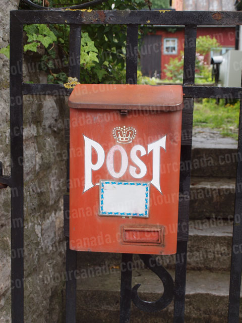 Red Post Box on a Fence | Cheap Stock Photo