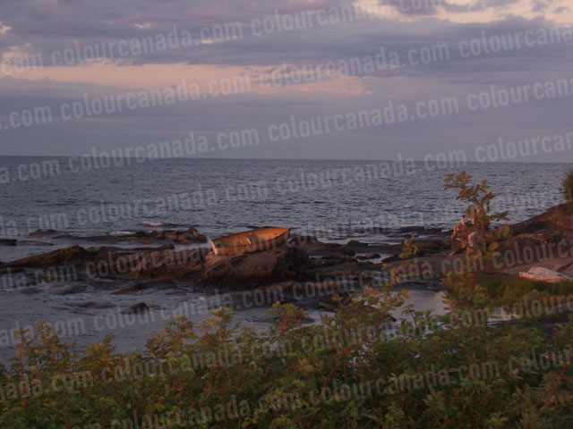 Sunset on a Row Boat with Rocky Shore | Cheap Stock Photo